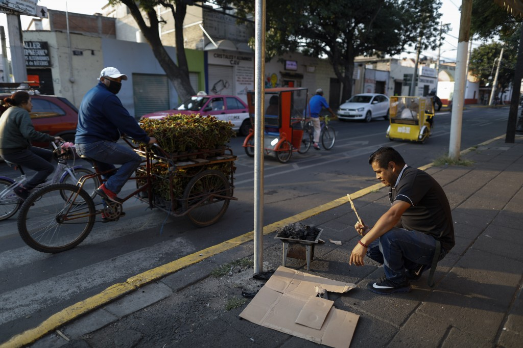 Jose Vargas stokes a carbon stove to heat tamales, as part of the street side breakfast stand he has operated for 15 years, with the help of his wife ...