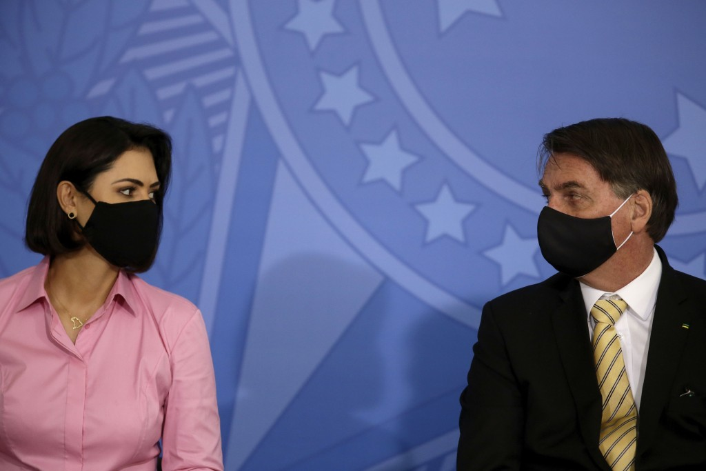 Brazil's President Jair Bolsonaro talks with his wife, first lady Michelle Bolsonaro, both wearing masks amid the COVID-19 pandemic, during an event p...