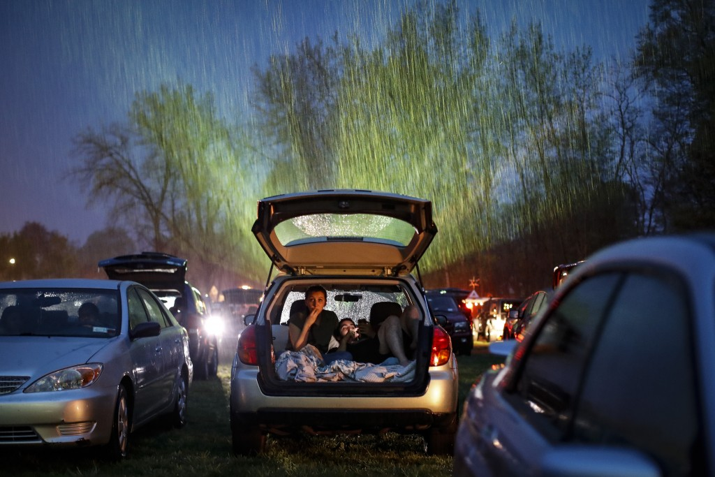 """Guests watch """"Trolls World Tour,"""" in the rain at the Four Brothers Drive In Theatre amid the coronavirus pandemic, Friday, May 15, 2020, in Amenia, N...."""