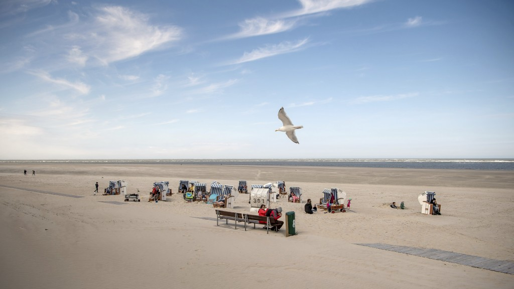 In this Saturday, May 16, 2020 photo a seagull flies over a small number of beach chairs on the island Spiekeroog, Germany. Germany's states, which de...
