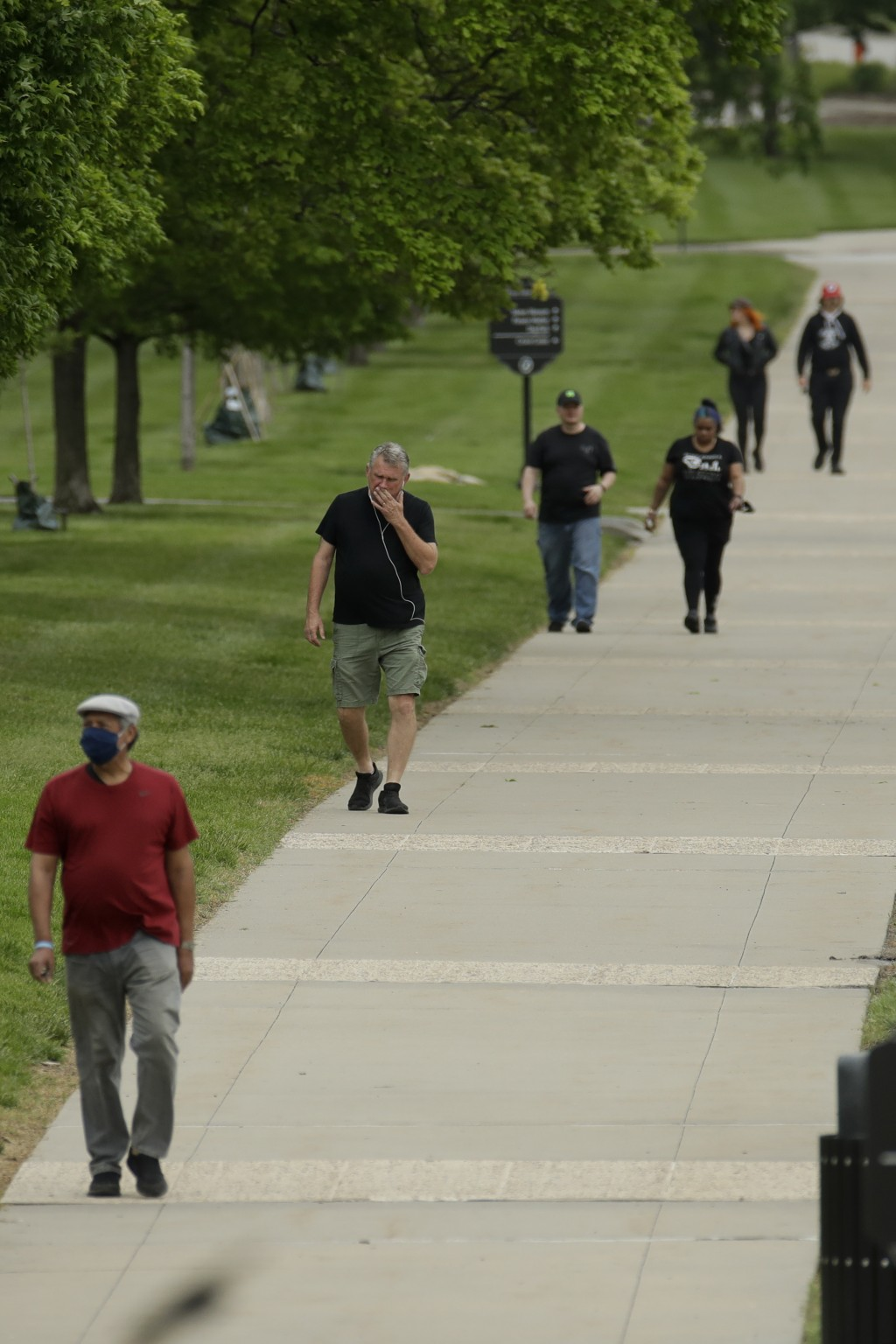 People walk in a park Friday, May 15, 2020 in Kansas City, Mo. The city lifted stay-at-home orders meant to stem the spread of coronavirus today allow...