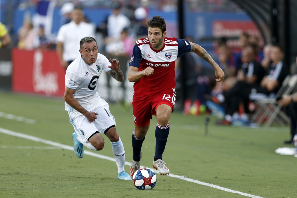 FILE - In this Aug. 10, 2019, file photo, FC Dallas defender Ryan Hollingshead plays the ball while Minnesota United forward Miguel Ibarra chases him ...