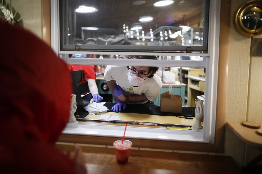 Workers wear personal protective equipment amid the coronavirus pandemic as they serve guests at the Four Brothers Drive In Theatre, Friday, May 15, 2...