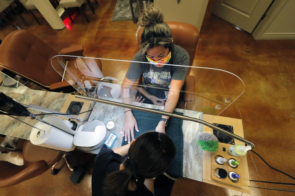 Customer Gabi Bustillo gets a manicure through new plexiglass partitions at Luxurie Nail Spa in Harahan, La., Friday, May 15, 2020. Once a hot spot fo...