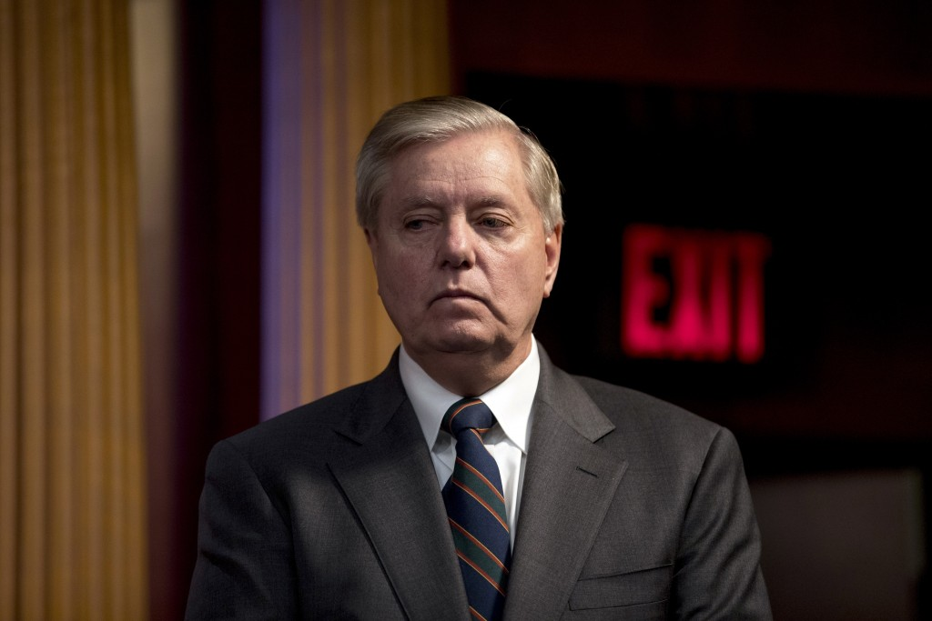 FILE - In this March 25, 2020, file photo Sen. Lindsey Graham, R-S.C., listens during a news conference about the coronavirus relief bill on Capitol H...