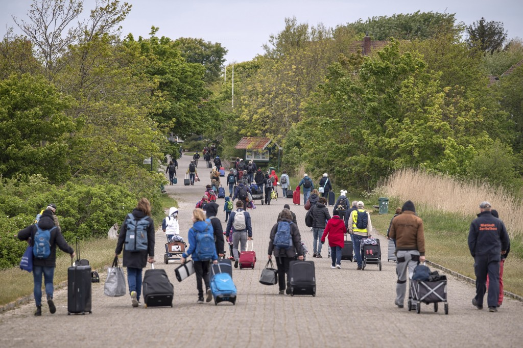 In this Saturday, May 16, 2020 photo, tourists with suitcases walk across the island of Spiekeroog, Germany. Germany's states, which determine their o...