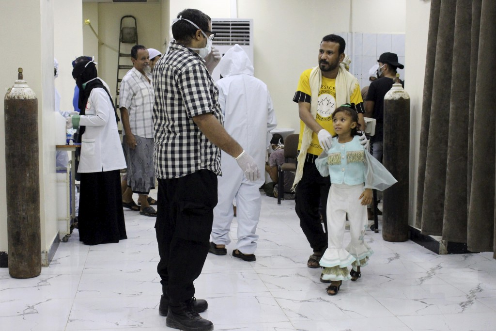 In this May 12, 2020 photo, Yemeni medical workers wearing masks and protective gear talk to patients at hospital in Aden, Yemen. People have been dyi...