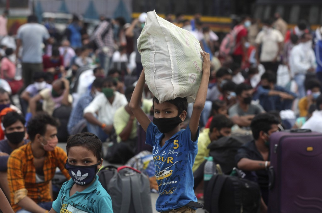 Children of migrant workers from other states wait outside a railway station to catch a train to return to their hometowns, in Mumbai, India, Friday, ...