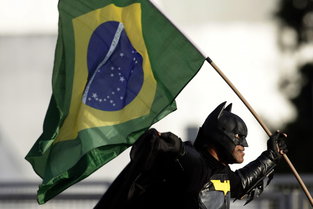A man dressed in a Batman costume and holding a national flag, joins a crowd gathered in front of the Planalto presidential palace to show their suppo...