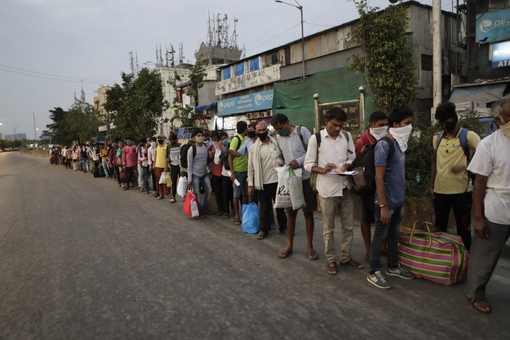 Migrant workers from other states line up to board buses for their onward journey by train to their destination, at Dharavi in Mumbai, India, Friday, ...