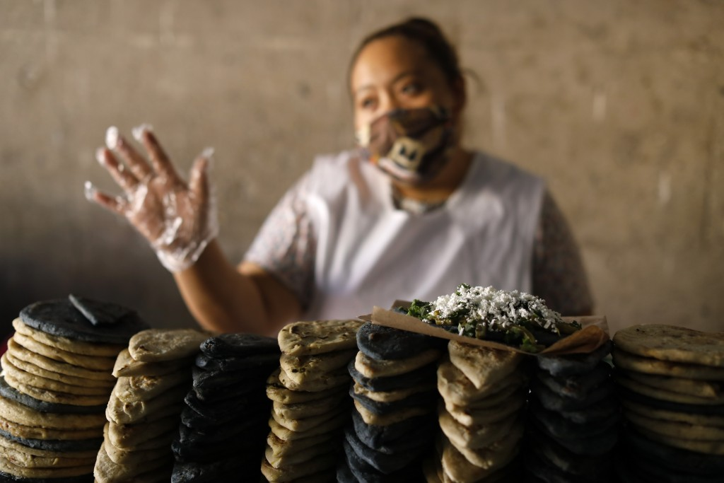 Eloisa Rojas Zamora wears a mask as she sells tlacoyos and sopes in a partially-open public market in the Xochimilco district of Mexico City, Friday, ...