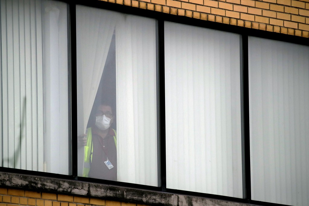 A worker in a face mask watches from a plant window as Missouri Gov. Mike Parson talks to the media outside Ford's Kansas City Assembly Plant Friday, ...