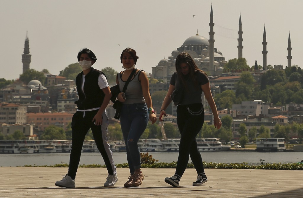 Turkish girls walk in Istanbul, backdropped by the Suleymaniye Mosque, Friday, May 15, 2020. Teenagers were able to leave their homes for the first ti...