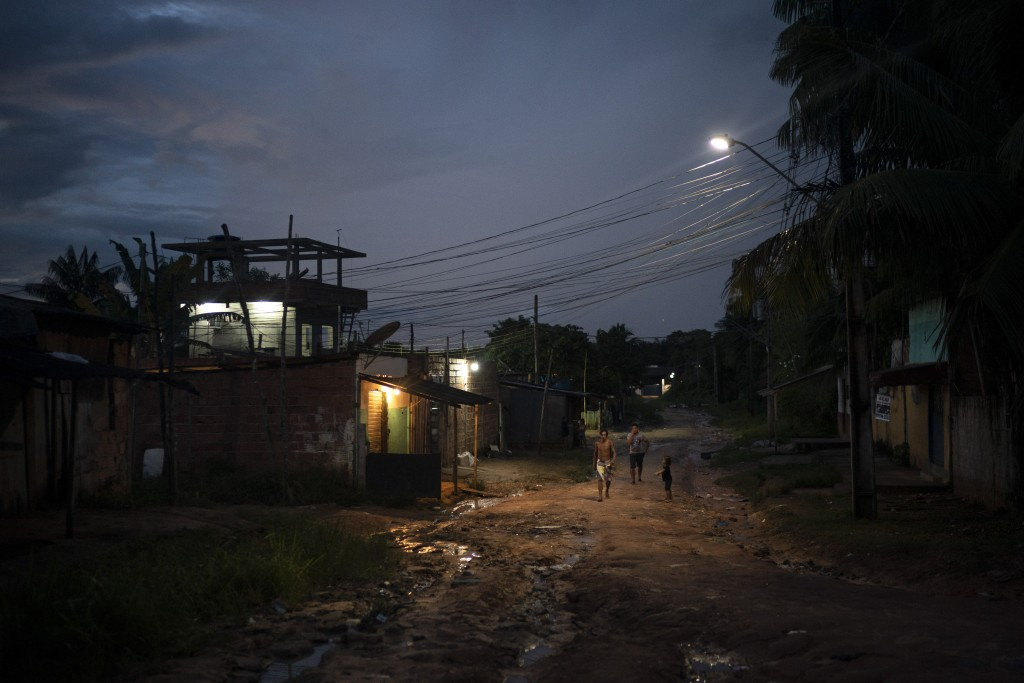In this May 10, 2020 photo, residents walk on a dirt road in the Park of Indigenous Nations community, in Manaus, Brazil. The South American country h...