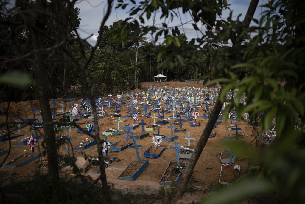 In this May 11, 2020 photo, graves for people who have died in the past month fill a new section of the Nossa Senhora Aparecida cemetery, amid the new...