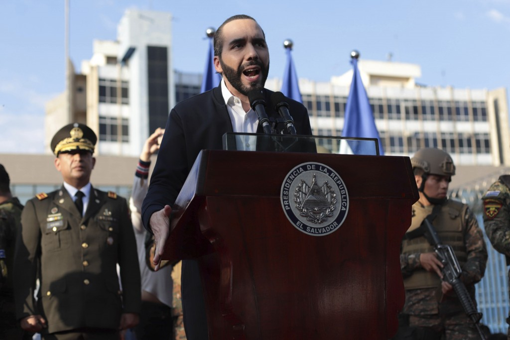 FILE - In this Feb. 9, 2020 file photo, El Salvador's President Nayib Bukele, accompanied by members of the armed forces, speaks to supporters outside...
