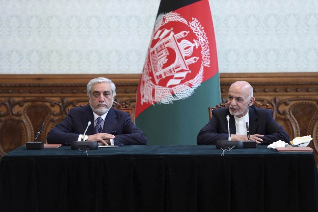 Afghan President Ashraf Ghani, right, and political rival Abdullah Abdullah, speak after they signed a power-sharing agreement at the presidential pal...
