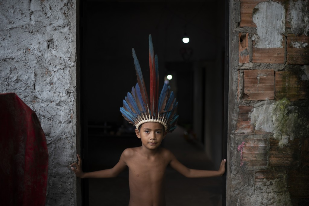In this May 10, 2020 photo, 9-year-old Pedro Henrique poses for a photo standing in the entrance of his home at the Park of Indigenous Nations communi...