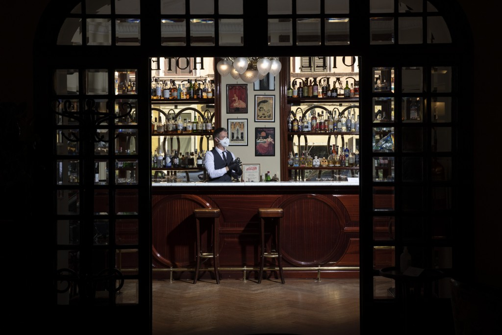 In this Monday, May 11, 2020 photo, barman Nicholas Pinna wears a protective face mask as he stands behind the cocktail bar of the art-deco style Loca...