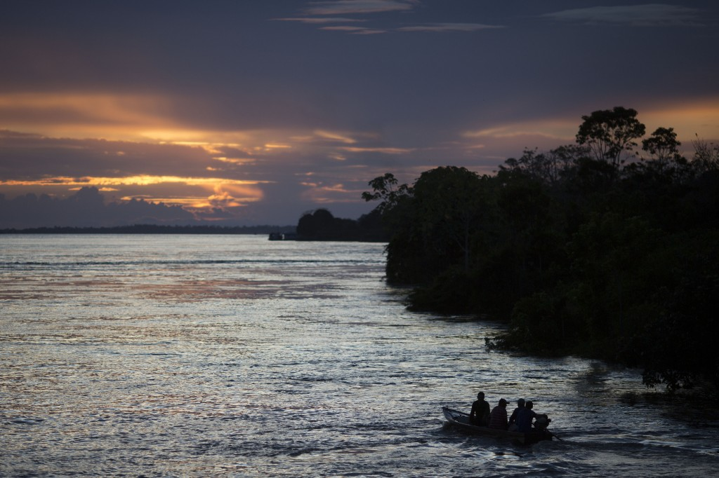 FILE - In this May 22, 2014 file photo, a small boat navigates on the Solimoes River near Manaus, Brazil. In the remote Amazon community of Betania, i...