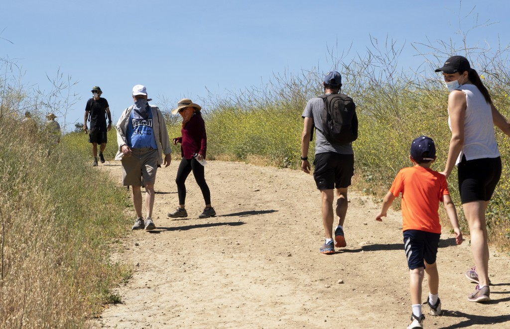 Visitors wear protective masks and social distance on a walk along a popular hiking trail along the Santa Monica mountain range in the Encino section ...