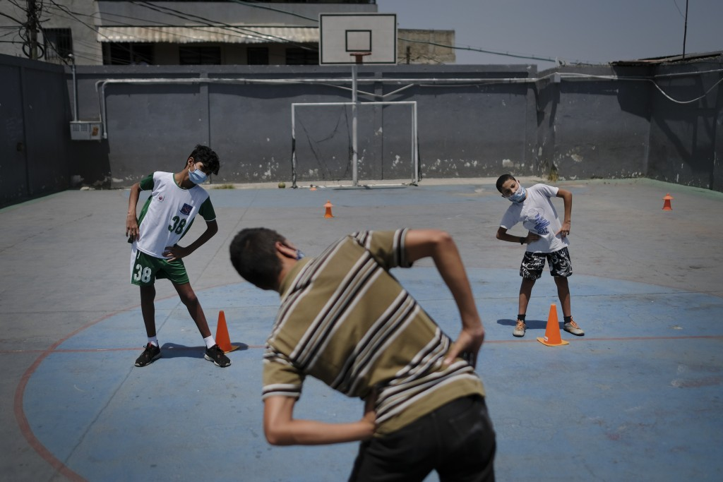 Children wearing protective face masks as a measure to curb the spread of the new coronavirus, stretch their muscles before they play a game of soccer...