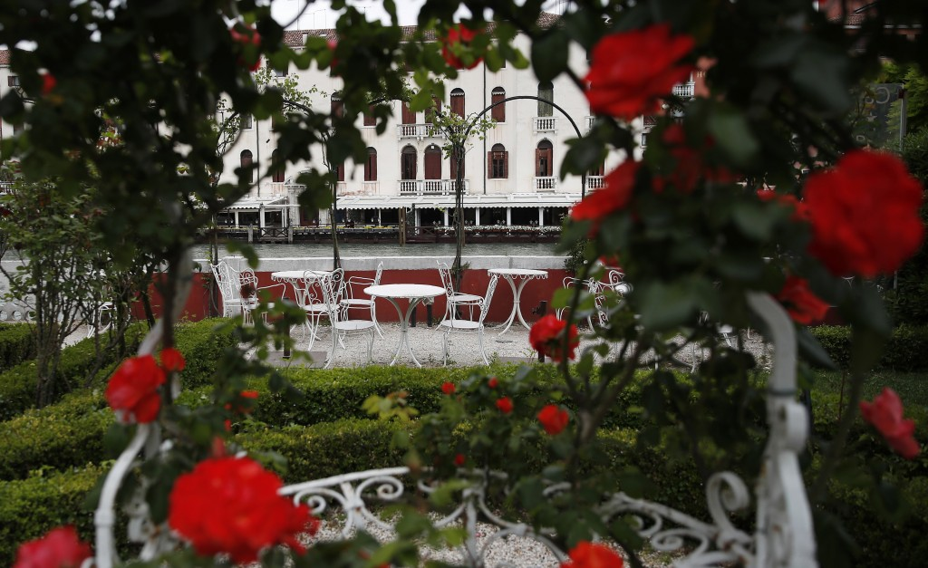 In this picture taken on Wednesday, May 13, 2020 rose bushes frame an empty garden overlooking a canal at the Ca' Nigra lagoon resort hotel along the ...