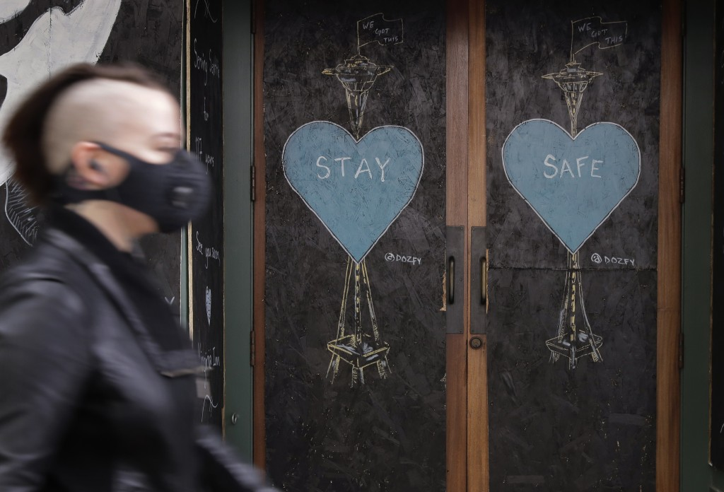 A pedestrian wearing a face mask walks past art by the street artist @dozfy, featuring the Space Needle on the boarded-up Virginia Inn Restaurant and ...