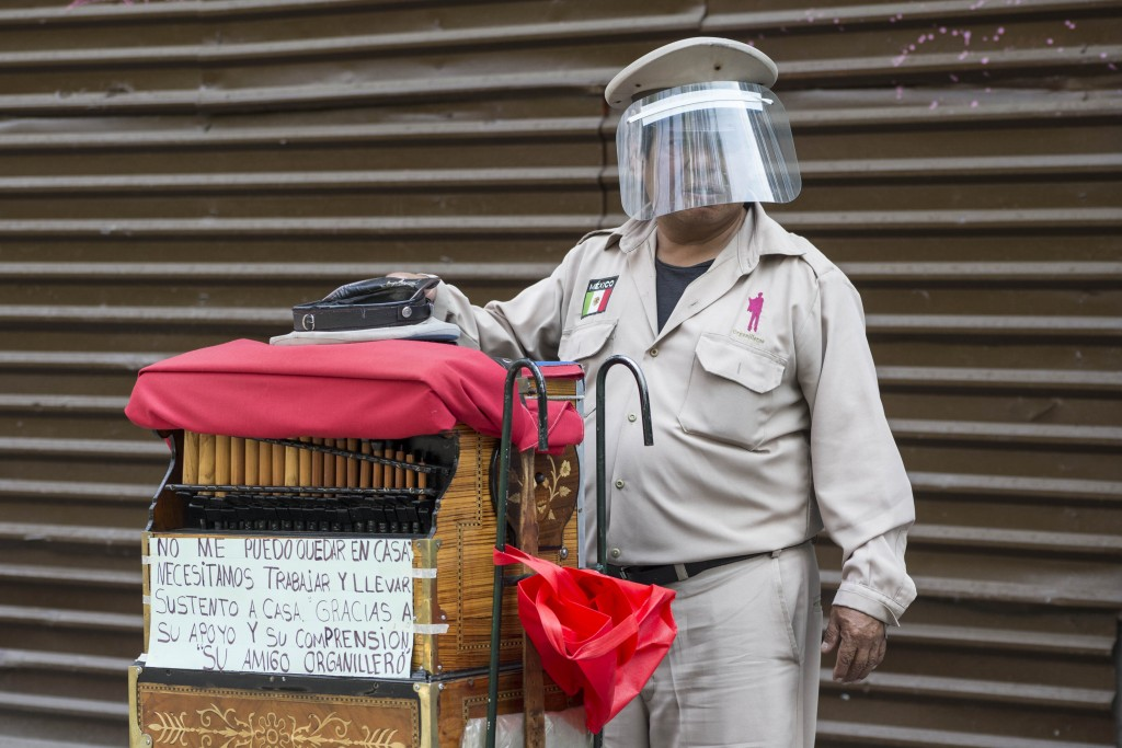 A barrel organ player wearing a face shield as a precaution against the spread of the new coronavirus, hopes for donations in Mexico City, Saturday, M...