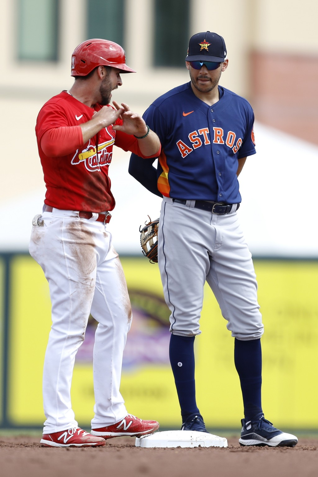 FILE - In this March 3, 2020, file photo, St. Louis Cardinals' Paul DeJong, left, talks to Houston Astros shortstop Carlos Correa during the second in...