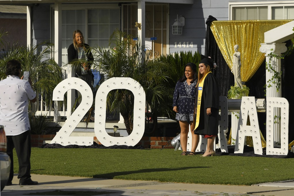 Kerry Martinez, right, who is graduating from California State University, Los Angeles has her picture taken in front of the home of Diane Scott, seco...