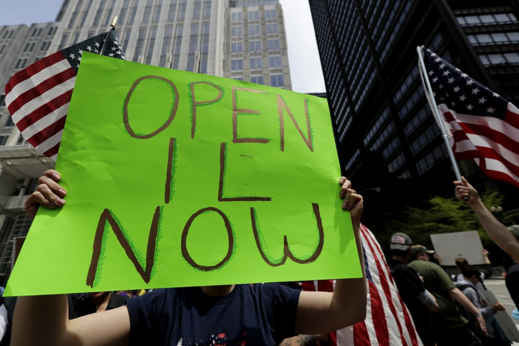 A protester holds a sign during a reopen Illinois rally outside Thompson Center in downtown Chicago, Saturday, May 16, 2020, during the coronavirus pa...