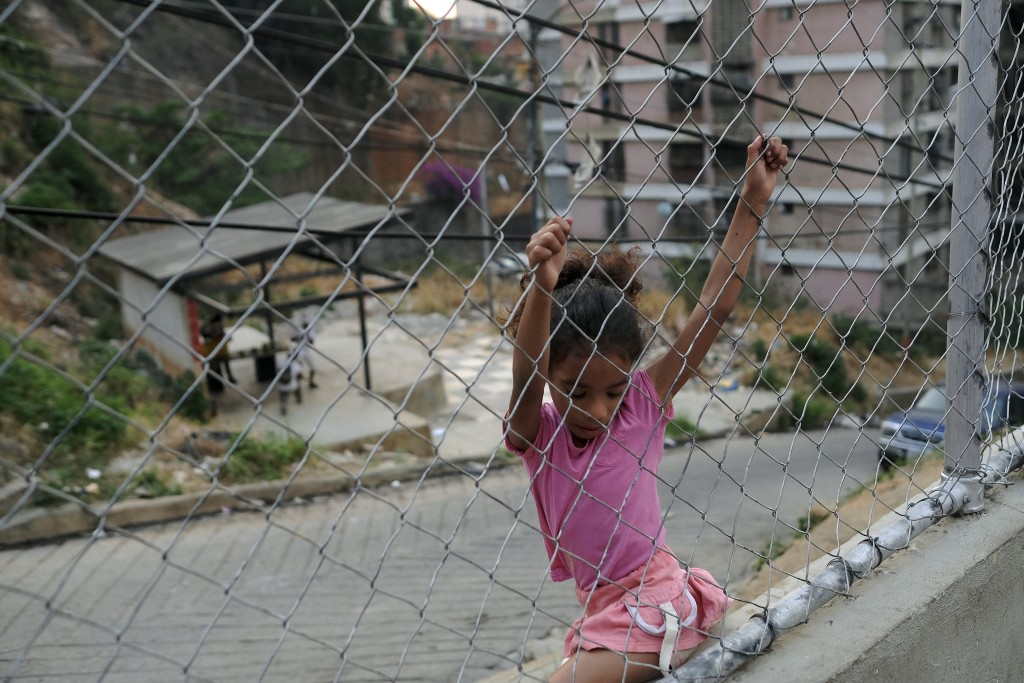 A child plays on a grid in the San Agustin neighborhood of Caracas, Venezuela, Saturday, May 16, 2020. President Nicolas Maduro is relaxing quarantine...