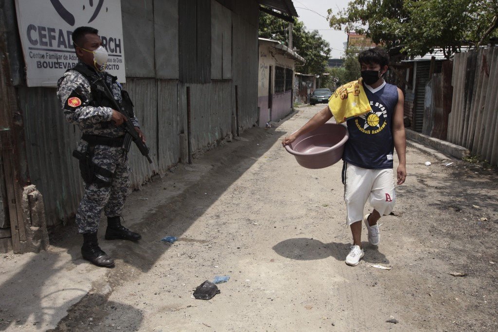 In this May 12, 2020 photo, a pedestrian walks past a National Civil Police officer, in San Salvador, El Salvador. The Human Rights Defense prosecutor...