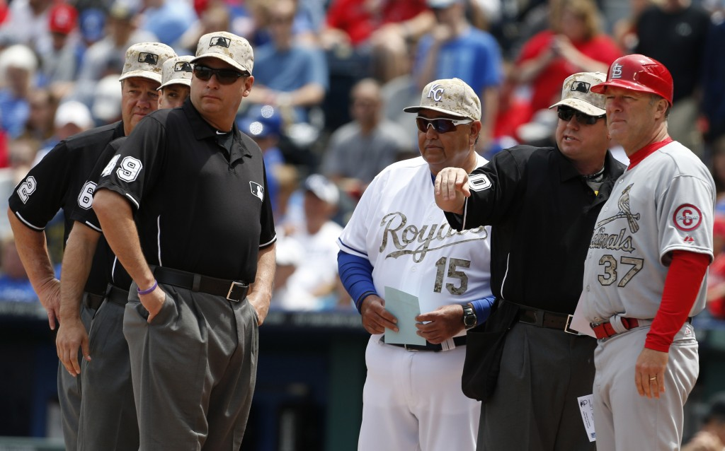 FILE - In this May 27, 2013, file photo, Kansas City Royals bench coach Chino Cadahia (15) and St. Louis Cardinals first base coach Chris Maloney (37)...