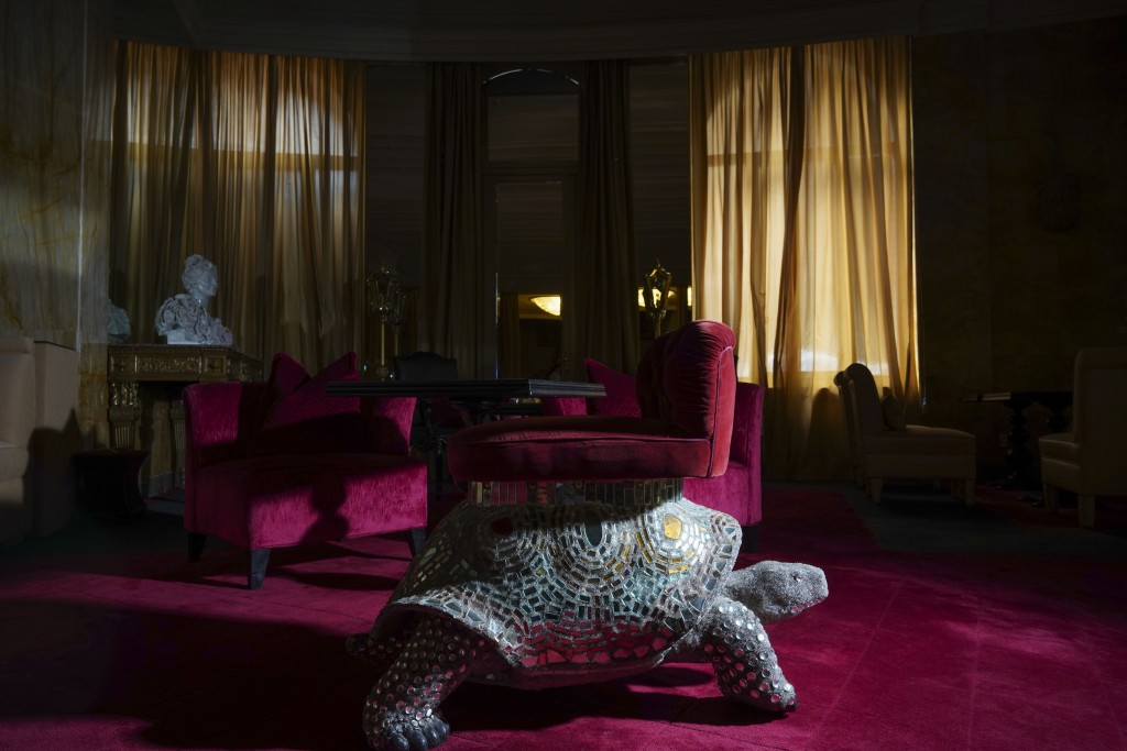 In this Wednesday, May 13, 2020 photo a turtle-shaped lounge chair is enveloped in the dark as curtains are closed at the Hotel Hassler, in Rome. The ...