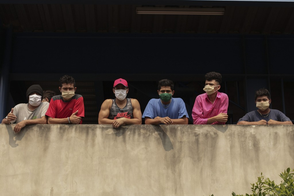 In this May 4, 2020 photo, men wearing protective face masks look out from a building where they are being held for violating a quarantine decreed by ...