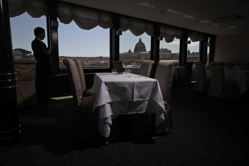 In this Monday, May 11, 2020 photo, Matteo Vasselli, concierge of Atlante Star Hotel, is silhouetted as he shows the restaurant of the hotel overlooki...