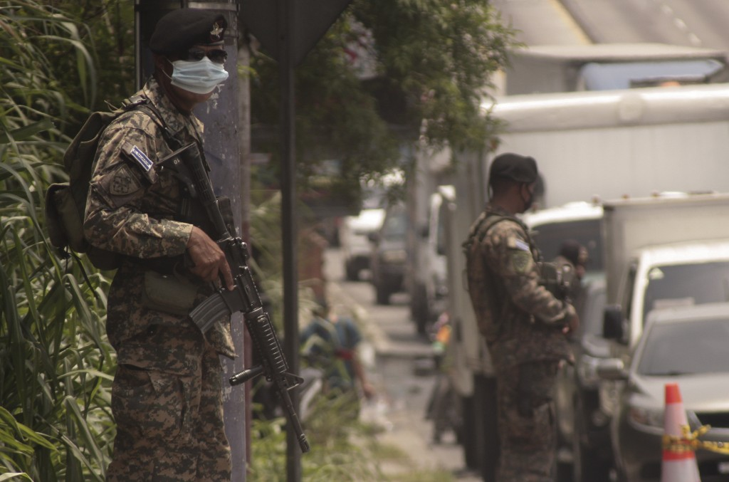 In this May 12, 2020 photo, soldiers serve as back up for National Civil Police officers at a checkpoint in San Salvador, El Salvador. On March 11, Pr...