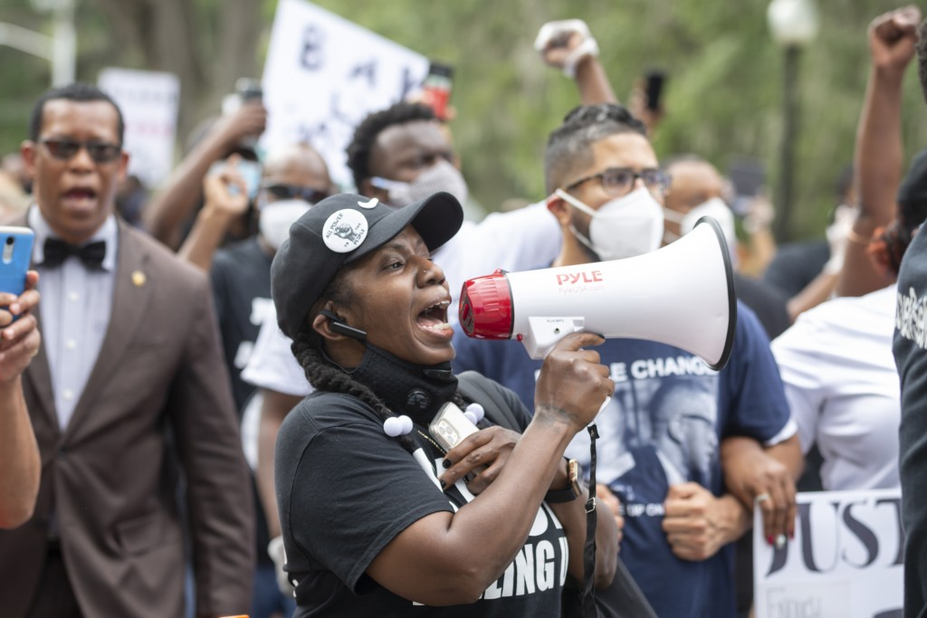 A group of protesters march from the Glynn County Courthouse in downtown to a police station after a rally to protest the shooting of Ahmaud Arbery, S...