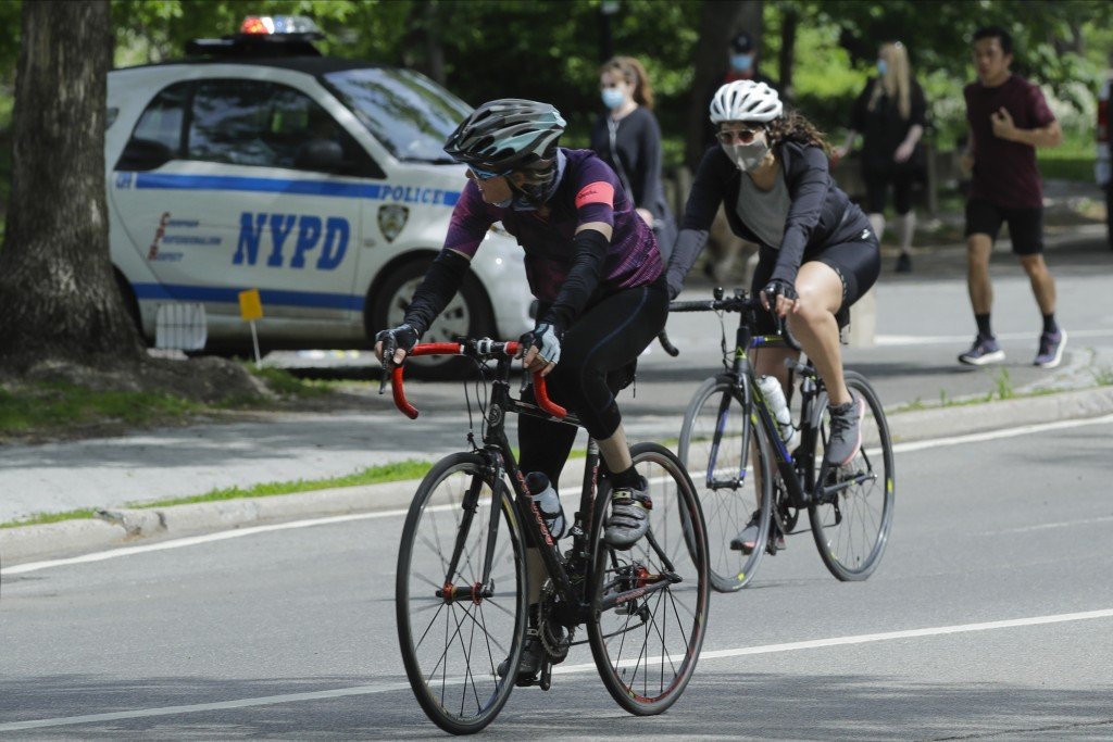 Cyclists wearing protective masks pass a New York Police vehicle near an entrance to Central Park during the coronavirus pandemic Saturday, May 16, 20...