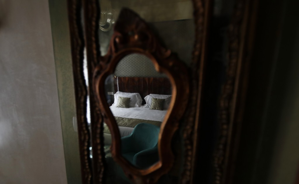 In this picture taken on Wednesday, May 13, 2020 a bed is reflected in the mirror in a bedroom of the Saturnia hotel, founded in 1908, in Venice, Ital...