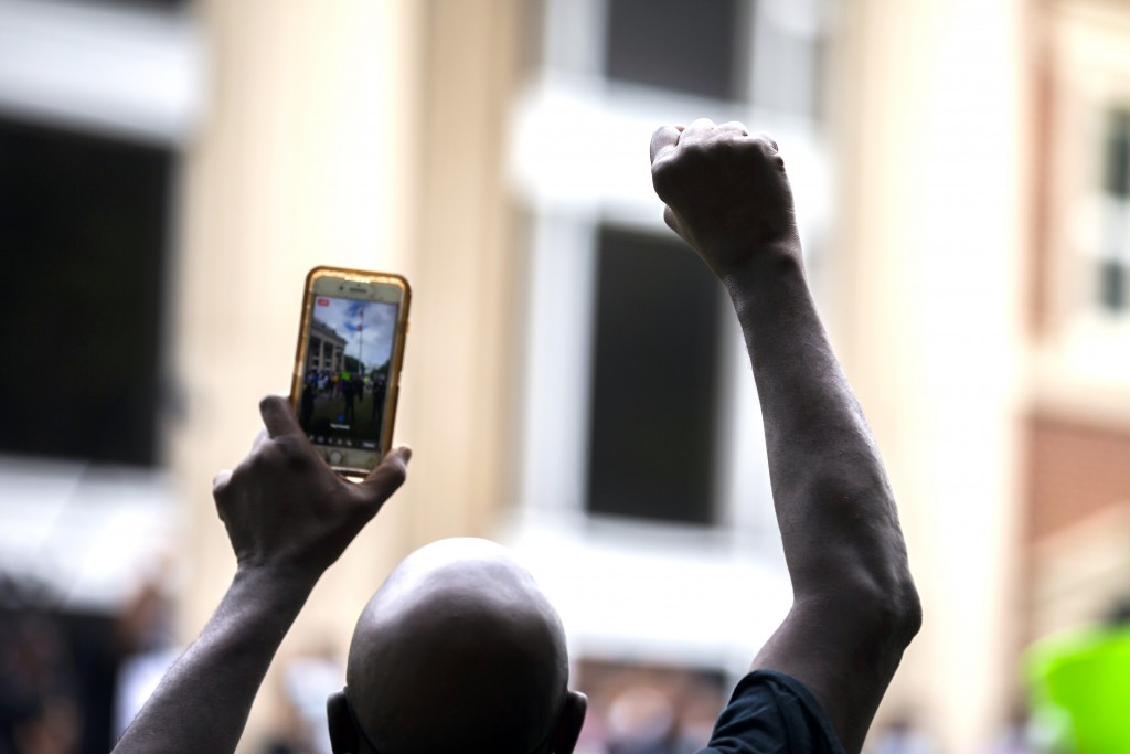 A protester raises his fist during a rally at the Glynn County Courthouse to protest the shooting of Ahmaud Arbery, Saturday, May 16, 2020, in Brunswi...