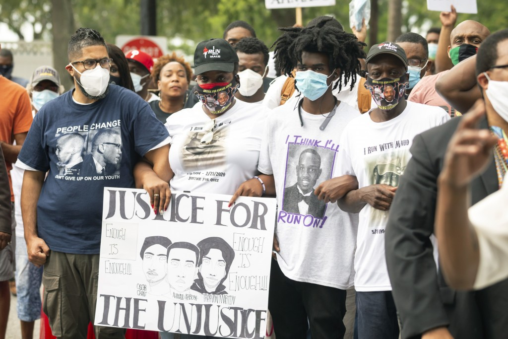 A group of protesters march from the Glynn County Courthouse to a police station after a rally to protest the shooting of Ahmaud Arbery, Saturday, May...