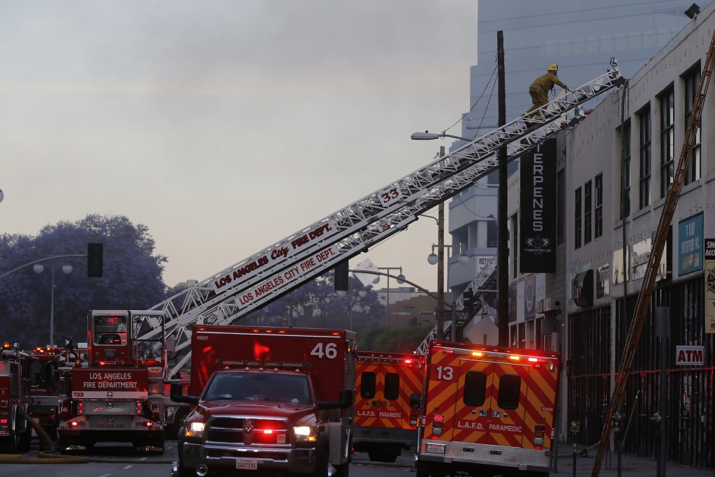 A Los Angeles Fire Department firefighter climb to the roof of a structure fire Saturday, May 16, 2020, in Los Angeles. (AP Photo/Damian Dovarganes)