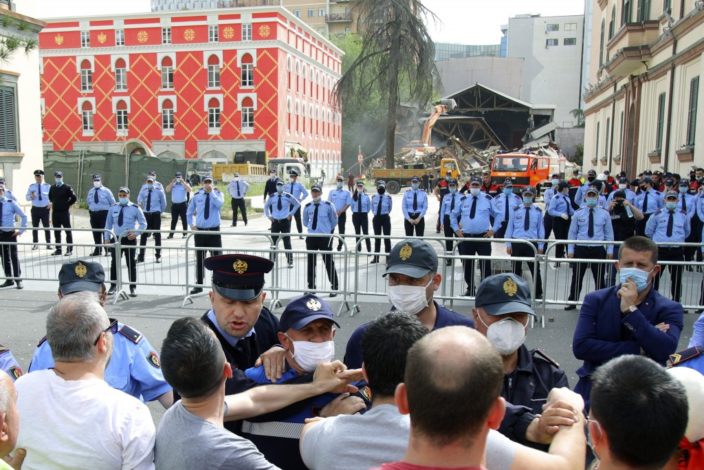 Protesters scuffle with police during the demolition of the national theater building in Tirana, Sunday, May 17, 2020. The government's decision to de...