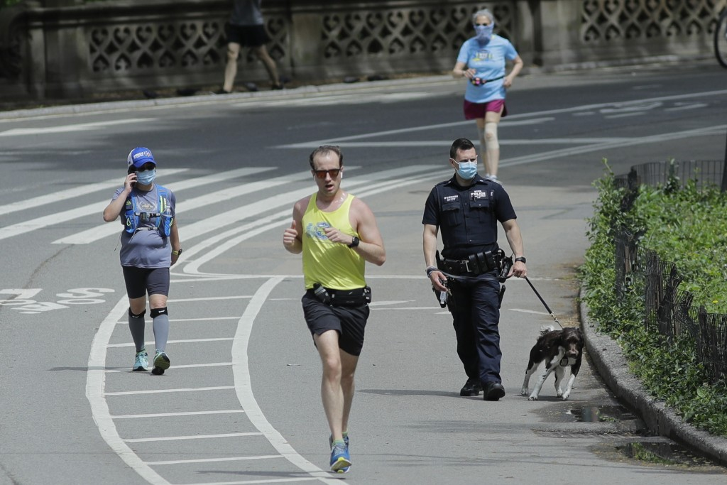 Runners pass a New York Police Officer as they warm weather during the coronavirus pandemic in Central Park Saturday, May 16, 2020, in New York. (AP P...