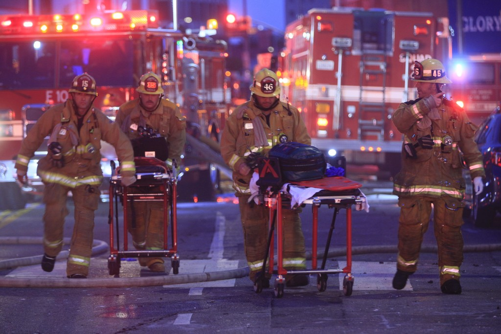 Los Angeles Fire Department firefighters push ambulance cots at the scene of a structure fire that injured multiple firefighters, according to a fire ...