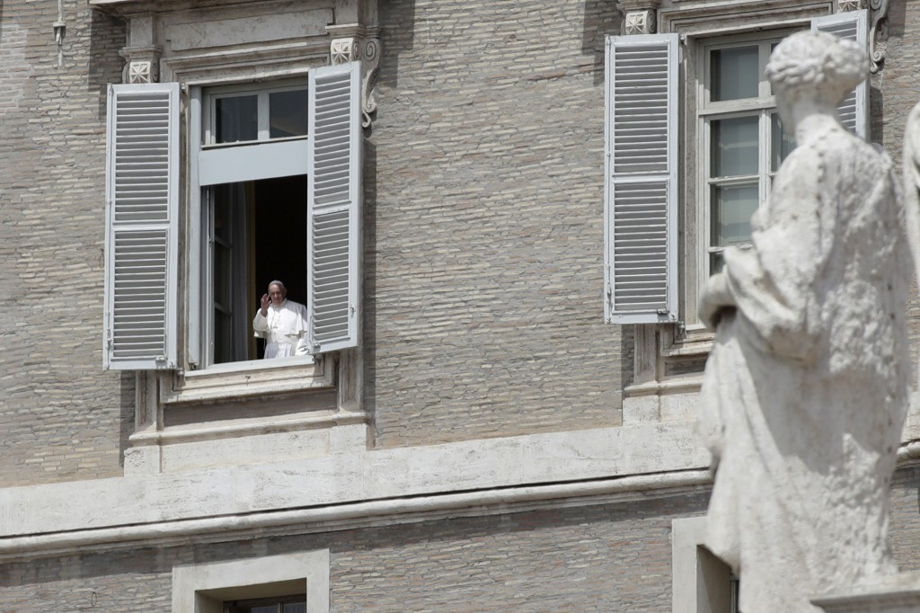 Pope Francis gives his blessing from his studio's window, overlooking St. Peter square, at the Vatican Sunday, May 17, 2020. During his weekly Sunday ...