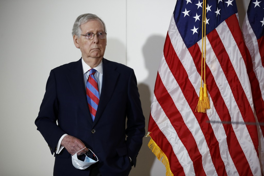 FILE - In this May 12, 2020, file photo Senate Majority Leader Mitch McConnell of Ky., holds a face mask used to protect against the spread of the new...